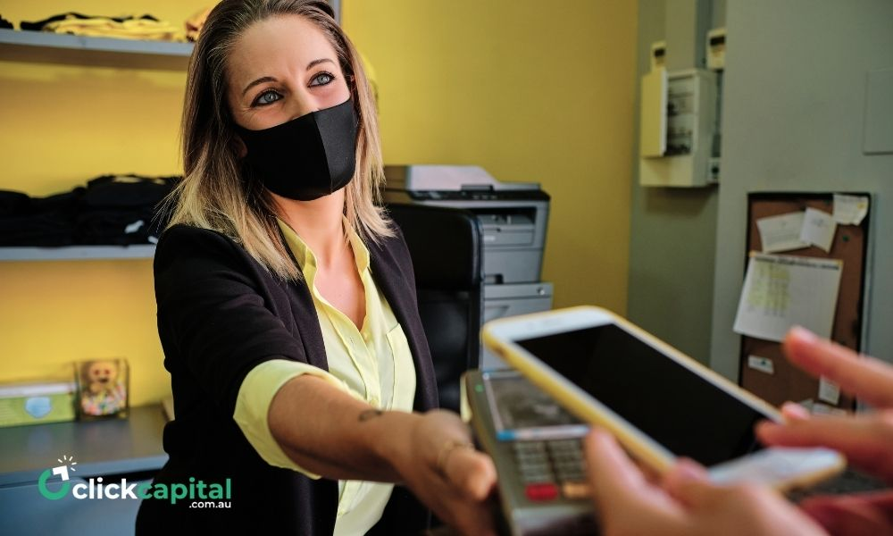 business owner with a mask doing Cashless transaction Using Smartphone